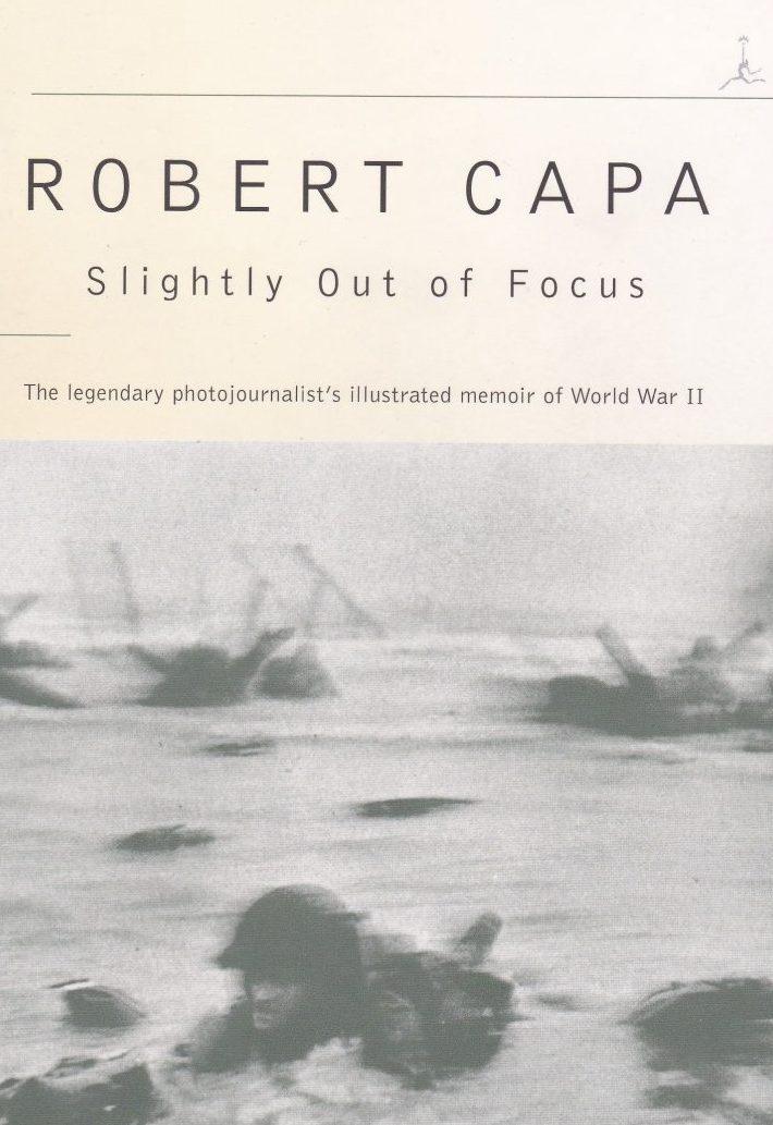 """""""Slightly out of focus"""" e o autobiografie înflorită, în care Capa povestește experiențele sale din al Doilea Război Mondial. Pe copertă, una dintre cele 11 imagini care au supraviețuit din Ziua Z, pe plaja botezată de americani """"Omaha""""."""
