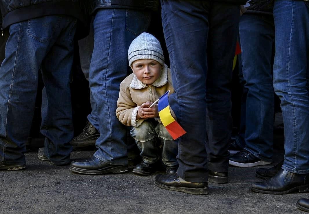 Un copil din Chișinău asistă la Centenarul Unirii, în Piața Marii Adunări Naționale din Capitala Republicii Moldova. FOTO: Andreea Alexandru